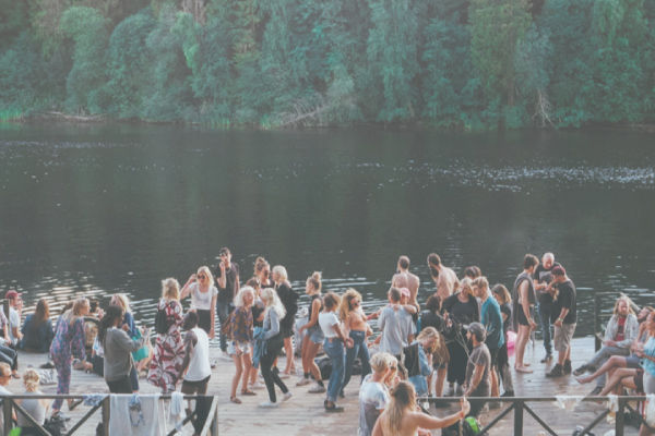 crowd having fun and hanging on the dock of a cottage home by the lake