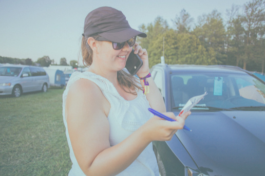 woman answering a phone call and taking notes while at a summer camp
