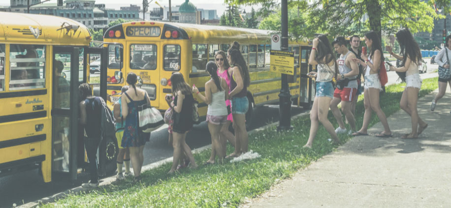bus riders embarking on a yellow school bus