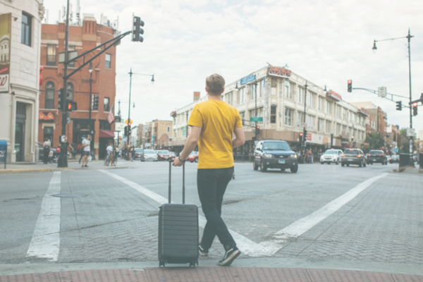 man with suitcase waiting for a ride at the corner of a street