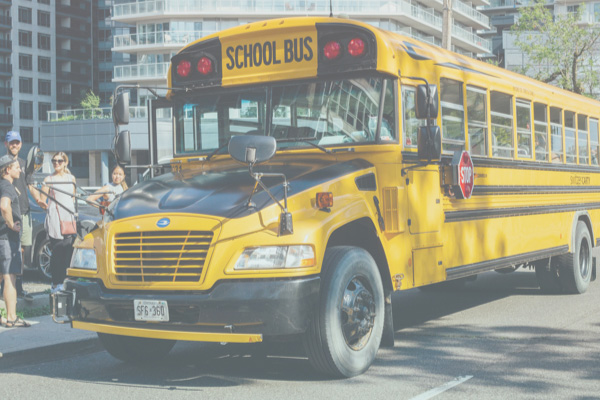 yellow school bus picking up riders on the side of the street
