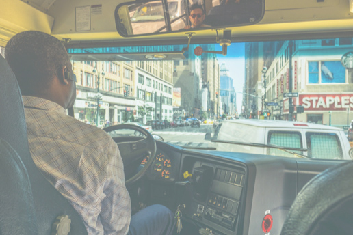 view from behind the bus driver looking ahead as the bus drives into busy city streets